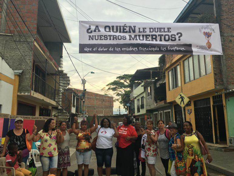 """Holmes, Wells and other activist mothers stand before a banner in Colombia that reads, """"Who feels for our dead? May the mothers' pain transcend borders."""" PHOTO COURTESY OF GLOBAL NETWORK OF  MOTHERS IN RESISTANCE."""