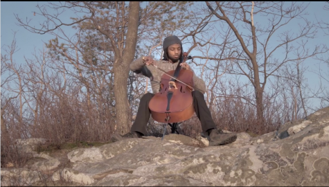 """Tasan Smith-Gandy playing his """"Pine Cello"""" composition at the top of Pine Cobble Trail. (Photo courtesy of Jay Corey.)"""